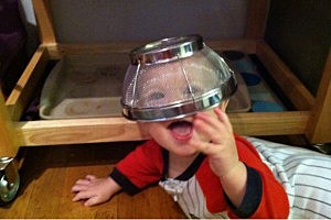 Baby with a strainer on his head
